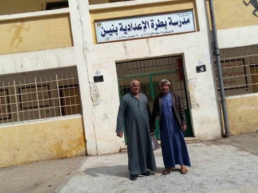 أحد الطلبة اليمنين السابقين مع معلمه عبد الغفار أمام مدرسة بقريته بمحافظة الدقهلية شمالي مصر.