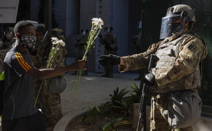 أحد المحتجين يقدم الزهور لعنصر من الحرس الوطني. (أ ب)