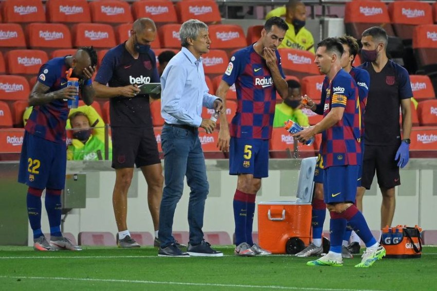 سيتيين مع لاعبي برشلونة خلال مواجهة أتلتيكو مدريد الثلاثاء. (أ ف ب)
