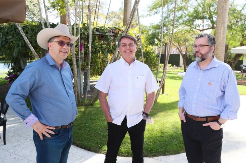 بولسونارو (وسط) والسفير الأمريكي (يسار) بلا كمامات. (رويترز)