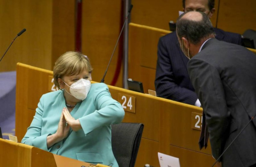 ميركل تحيي الأعضاء على طريقة كورونا في البرلمان الأوروبي. (أ ب)