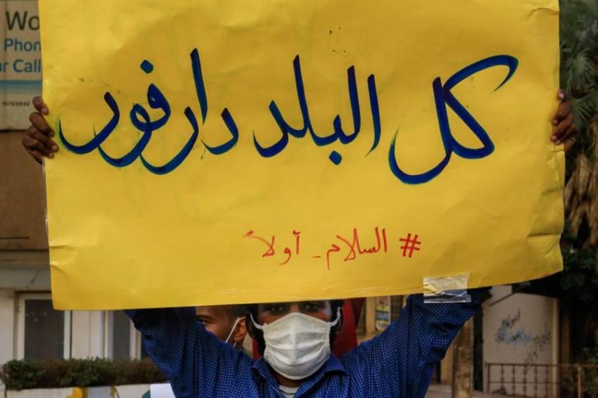 متظاهر من نيرتتي بالسودان يرفع لافتة «كل البلد دارفور». (أ ف ب)