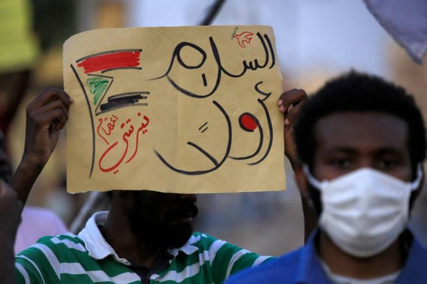 متظاهر من نيرتتي بالسودان يرفع لافتة «السلام أولاً». (أ ف ب)