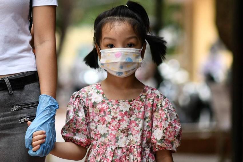 فتاة ترتدي الكمامة في فيتنام. (أ ف ب)