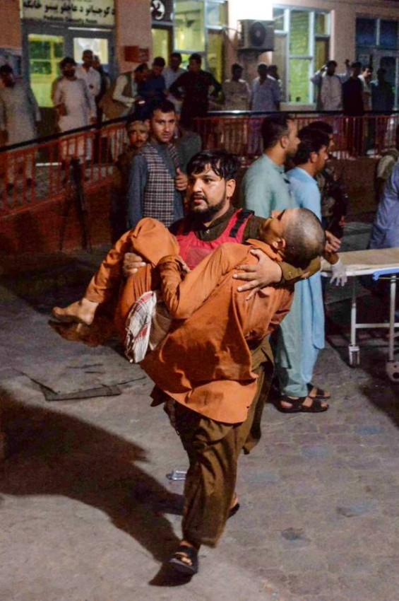 شخص يحمل مصاباً جراء تفجيرات استهدفت سجناً في أفغانستان. (أ ف ب)