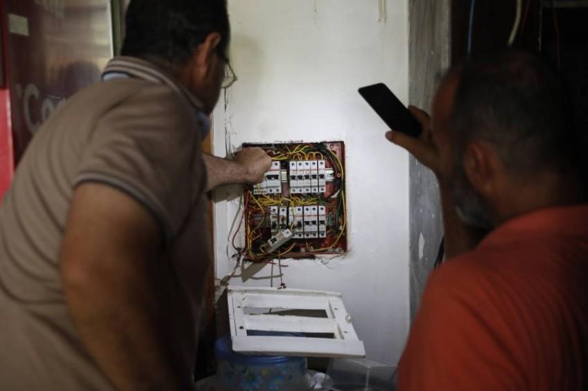 عامل يصلح الكهرباء بأحد مقاهي لبنان. (أ ب)
