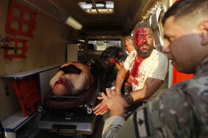 جندي لبناني يفحص رجلا جريحا في سيارة اسعاف في موقع الانفجار. (أ ب)