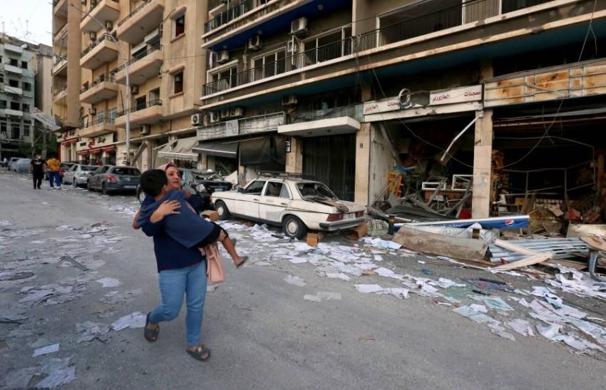سيدة وطفل وسط الدمار في شوارع بيروت. (رويترز)