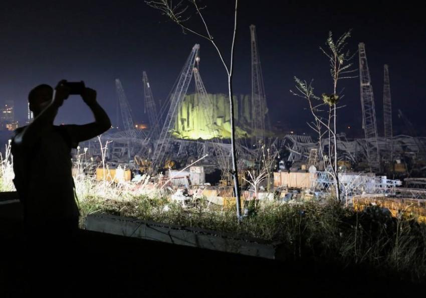 شخص يلتقط صورة لموقع انفجار بيروت. (رويترز)