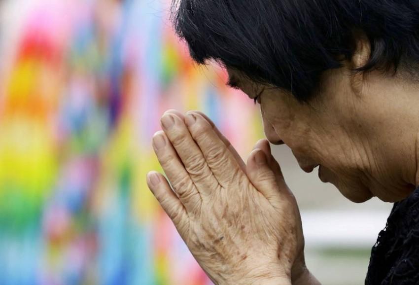 اليابانيون يصلون لضحايا نجازاكي. (رويترز)