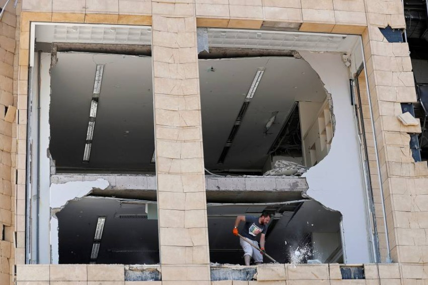 A man removes debris from a damaged building near the site of Tuesday's blast in Beirut's port area, Lebanon August 8, 2020. REUTERS/Thaier Al-Sudani