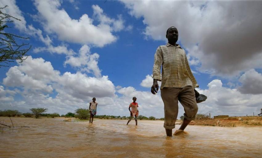 أشخاص يخوضون في مياه الفيضانات في السودان. (أ ف ب)