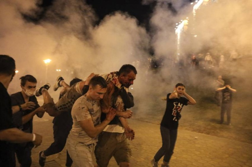 متظاهرون يحملون مصاباً خلال اشتباكات مع الشرطة في يبلاروس. (أ ب)