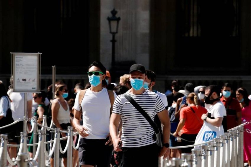 أشخاص أمام متحف اللوفر في باريس. (رويترز)