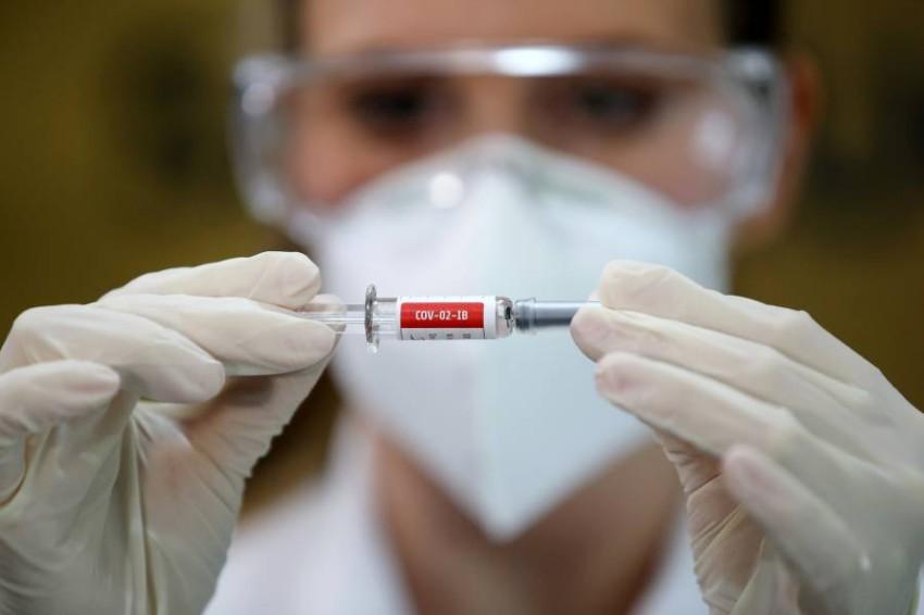 ممرضة تحمل عينة من لقاح قيد التجربة ضد كورونا. (رويترز)
