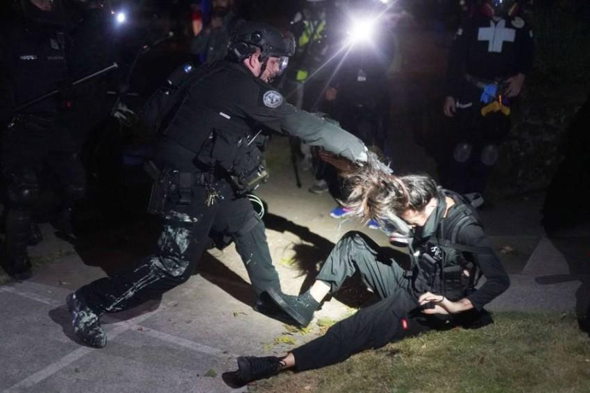 شرطي يمسك محتجة من شعرها خلال احتجاجات في بورتلاند. (أ ف ب)