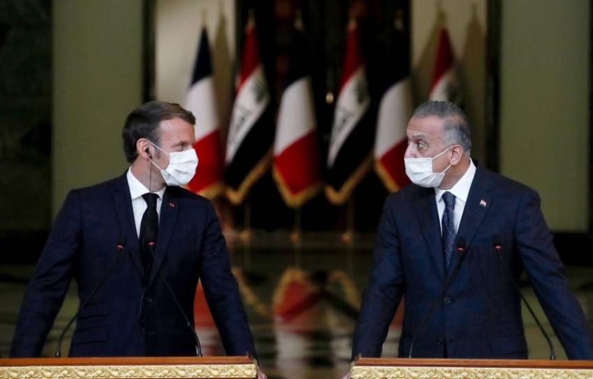 مصطفى الكاظمي وإيمانويل ماكرون خلال مؤتمر صحفي في بغداد. (أ ف ب)
