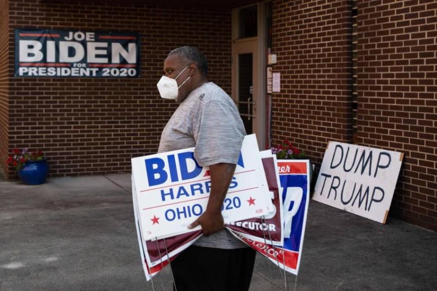 أحد أنصار المرشح الديمقراطي جو بايدن يحمل ملصقات مؤيدة له في أوهايو. (أ ف ب)