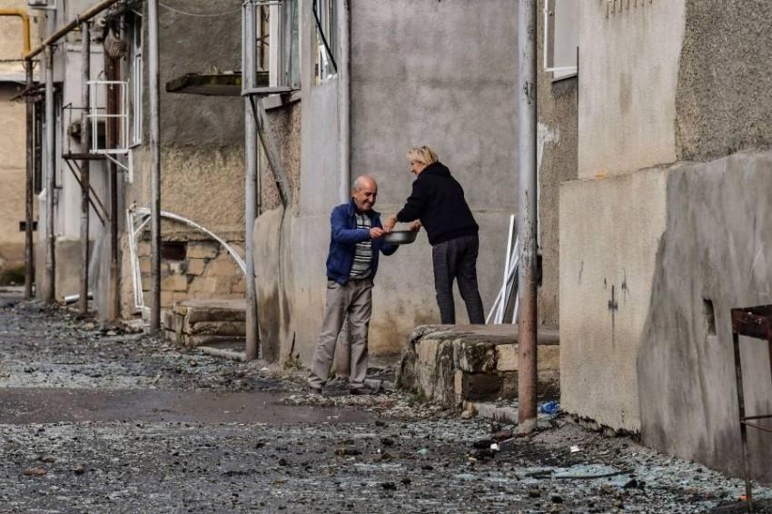 سكان يتبادلون الطعام وسط الدمار في ستيباناكرت. (أ ف ب)