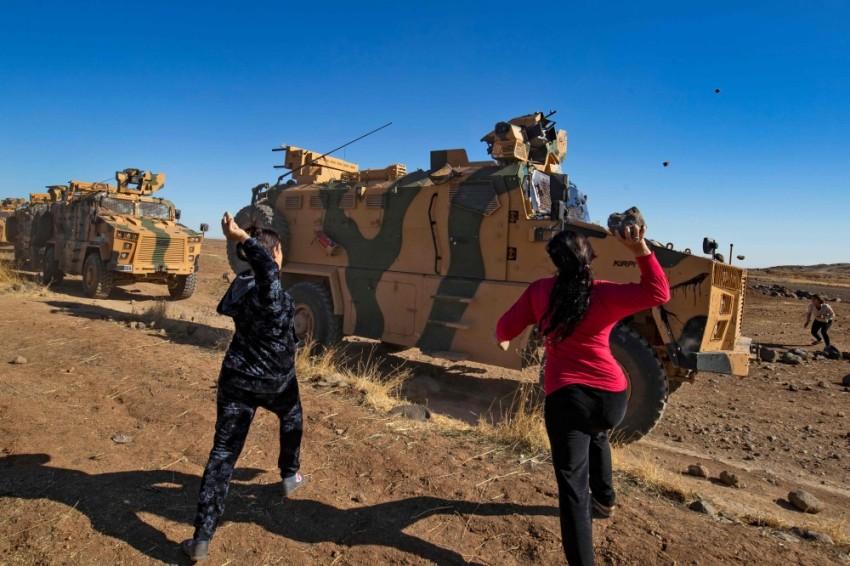 سوريون يقذفون عربة عسكرية تركية بالحجارة في محافظة الحسكة. (أ ف ب)