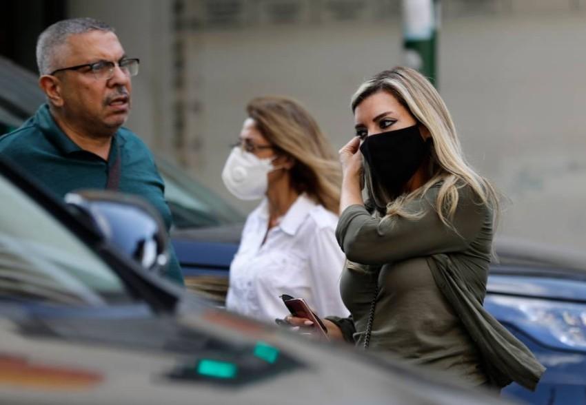 سيدة تضبط وضع كمامتها وهي تسير في أحد شوارع بيروت. (أ ف ب)