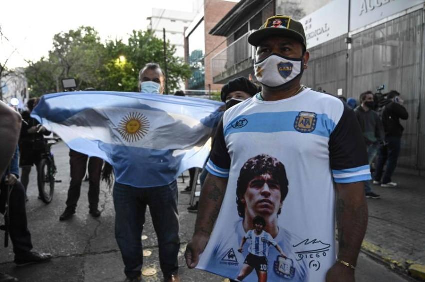 أنصار مارادونا يترقبون أخباره أمام المستشفى الذي يعالج فيه. (أ ف ب)
