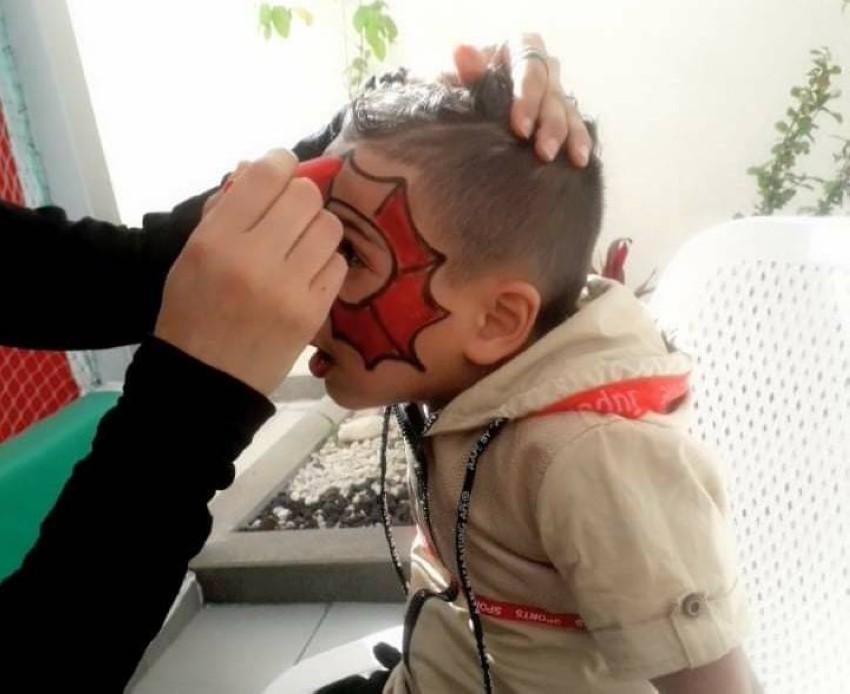 الفنانة التشكيلية نهيل زيدية خلال رسمها على وجه أحد الأطفال. (الرؤية)