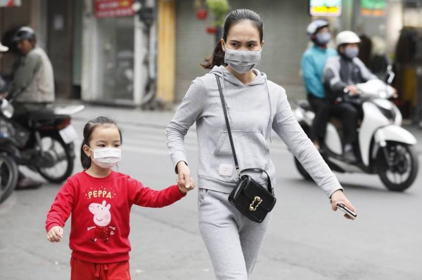 أم وطفلتها في أحد شوارع العاصمة هانوي. (إي بي أيه)