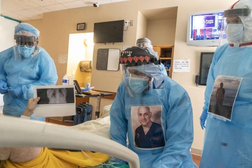 فريق طبي يتحدث إلى أحد مرضى كوفيد-19. (أ ف ب)