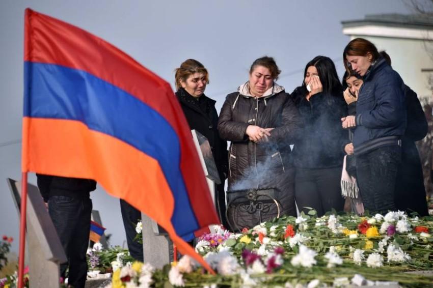 أسرة أرمينية تزور قبر أحد ضحايا الحرب الأخيرة في قره باغ. (أ ف ب)