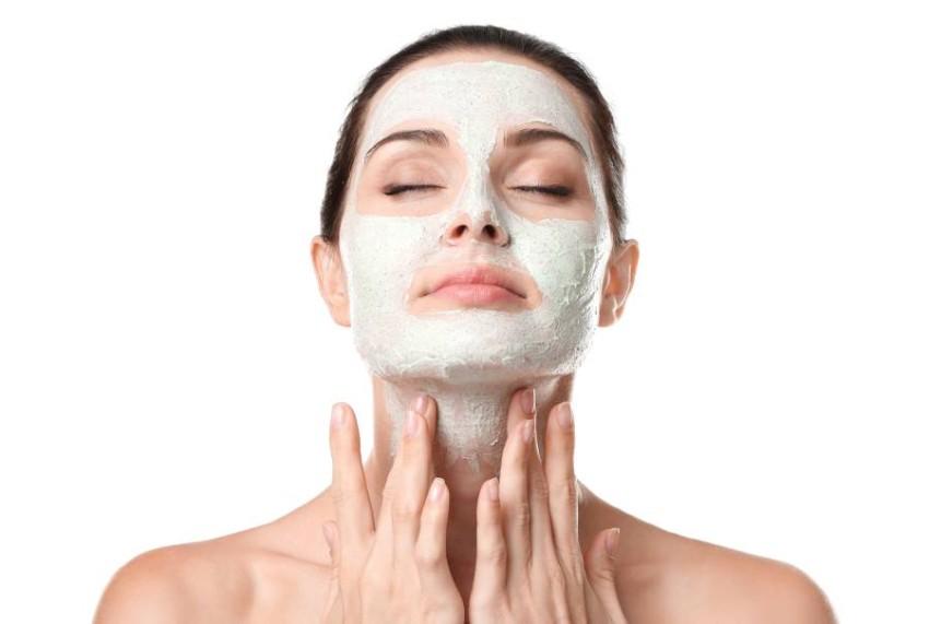 Beautiful young woman applying scrub mask on face, closeup