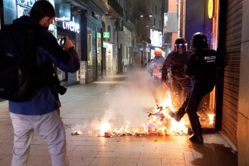 أفراد شرطة يحاولون إخماد حرائق أضرمها المتظاهرون. (إي بي أيه)