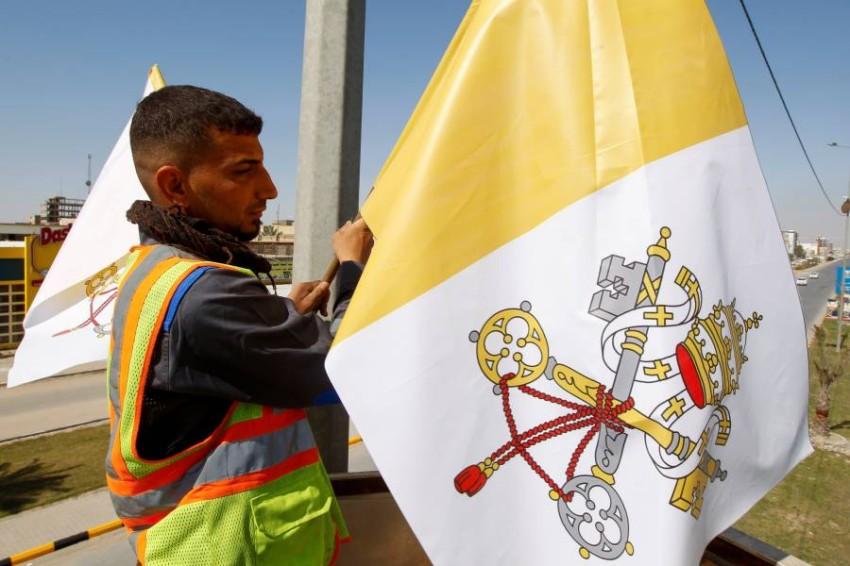 عامل يثبت علم الفاتيكان على عمود في مدينة النجف العراقية قبيل زيارة البابا فرنسيس. (رويترز)