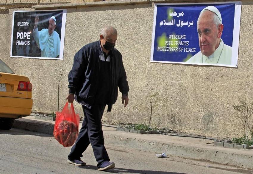 رجل يمر بأحد ملصقات الترحيب بزيارة البابا في بغداد. (أ ف ب)