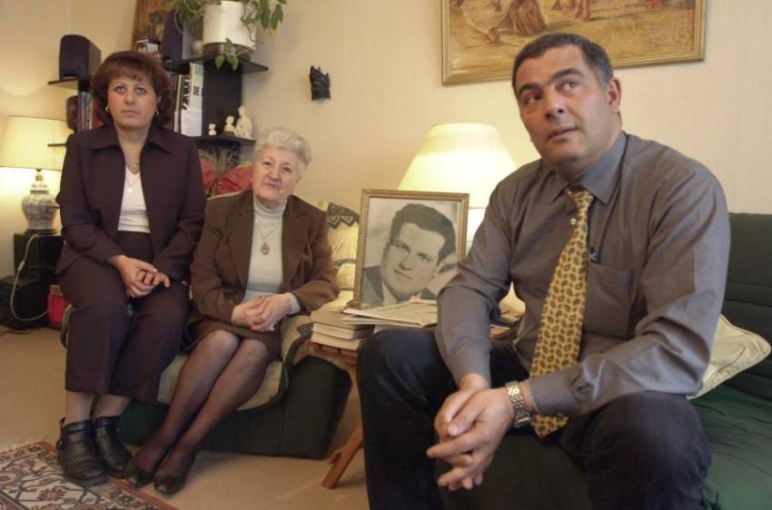 أفراد من عائلة الزعيم الجزائري بومنجل مع صورته. (أ ف ب)