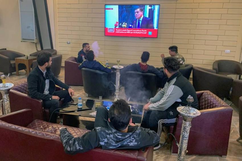 ليبيون يتابعون كلمة رئيس الحكومة على شاشات التلفزيون. (رويترز)