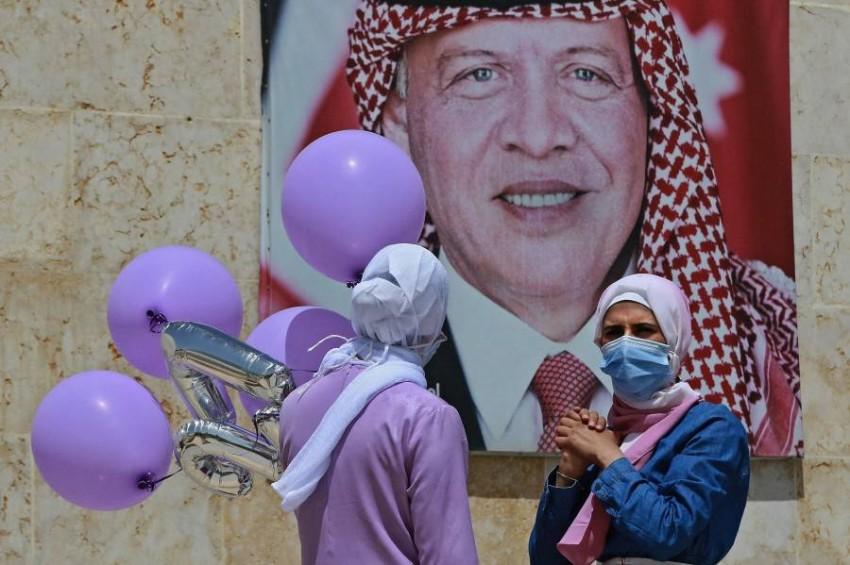 ملصق يحمل صورة ملك الأردن في أحد شوارع عمان.(أ ف ب)