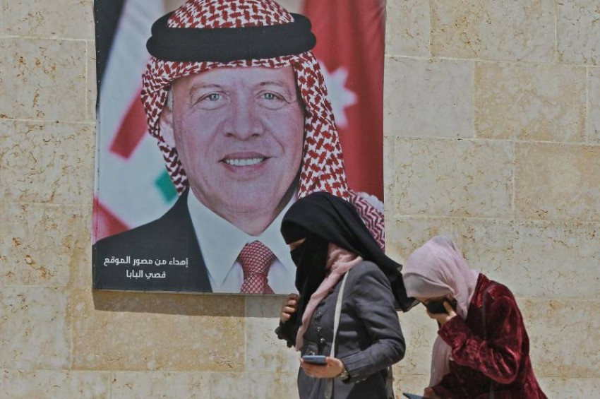 Women walk past a poster of Jordan's King Abdullah II on a street in the capital Amman, on April 6, 2021, after a security crackdown revealed tensions in the monarchy. (Photo by Khalil MAZRAAWI / AFP)