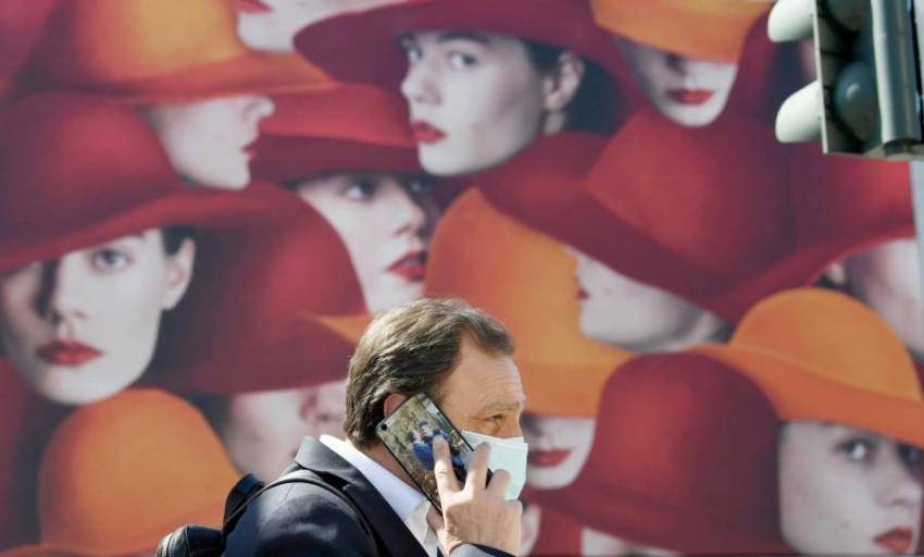 أحد المارة يرتدي الكمامة في ميلانو. (إي بي أيه)