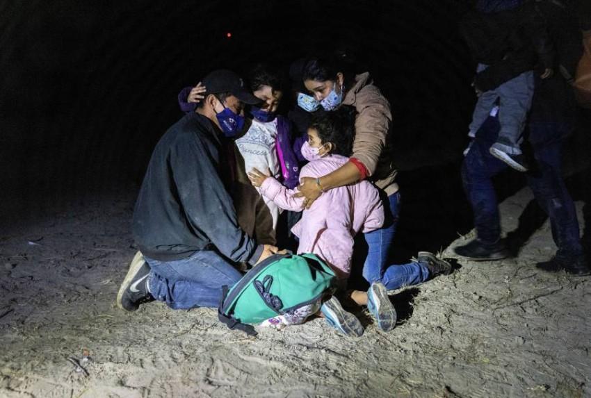 أسرة تحتضن أطفالها بعد العبور إلى الأراضي الأمريكية من المكسيك. (أ ف ب)