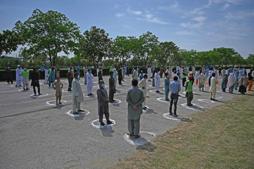 المستفيدون من الحملة في إسلام أباد يراعون إجراءات التباعد الاجتماعي. (أ ف ب)