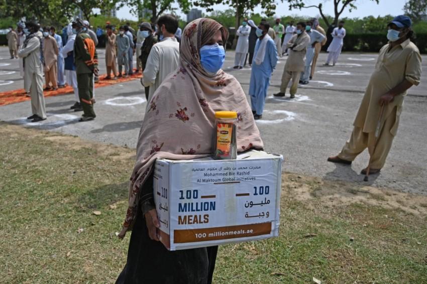 سيدة تحمل حصتها من المواد الغذائية في إسلام أباد. (أ ف ب)