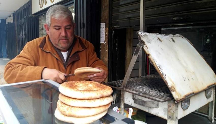 لبناني يجهز الكعك الشعبي لبيعه على عربته.(رويترز)