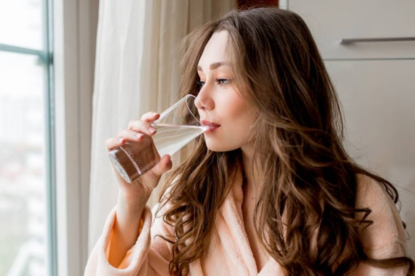 Pretty woman in bathrobe drinking fresh at home.