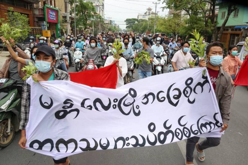 متظاهرون يحملون لافتات الإضراب في ميانمار. (إي بي أيه)