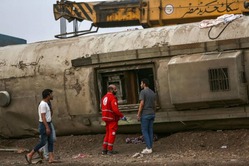A paramedic speaks with a man next to an overturned passenger carriage at the scene of a railway accident in the city of Toukh in Egypt's central Nile Delta province of Qalyubiya on April 18, 2021. - The train accident in Egypt left 97 wounded on April 18 after it derailed off its tracks heading northwards from the capital Cairo, the health ministry said, in the latest railway disaster. Eight carriages derailed off the tracks as the train headed to Mansoura, about 130 kilometres north of Cairo. (Photo by Ayman Aref / AFP)
