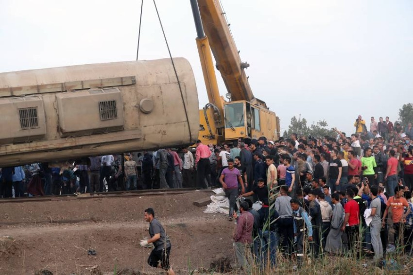epa09143869 A crane lifts a damaged carriage of a passenger train that was derailed in Toukh, Al Qalyubia Governorate, north of Cairo, Egypt, 18 April 2021. According to the ministry of health, 97 people were injured when several wagons of a passenger train that was heading to the city of Mansoura came off the rails. EPA/KHALED ELFIQI