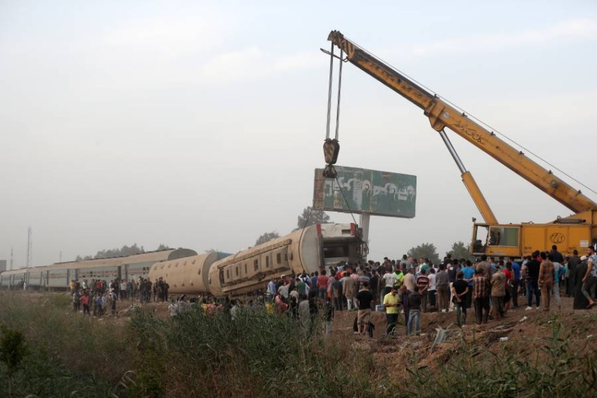 epa09143872 A crane lifts a damaged carriage of a passenger train that was derailed in Toukh, Al Qalyubia Governorate, north of Cairo, Egypt, 18 April 2021. According to the ministry of health, 97 people were injured when several wagons of a passenger train that was heading to the city of Mansoura came off the rails. EPA/KHALED ELFIQI