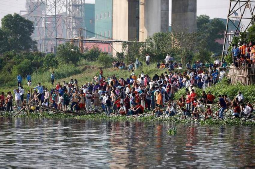 أقارب الضحايا على ضفة أحد الأنهار في حادث مماثل. (رويترز - أرشيفية)