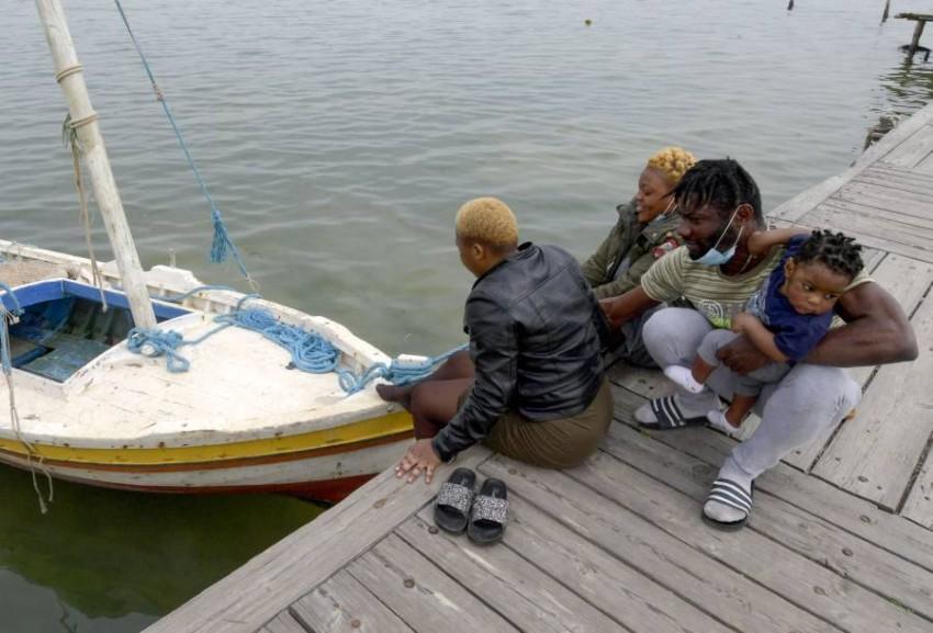 لاجئون تم إنقاذهم من الغرق يجلسون عند أحد شواطئ تونس.(أي بي أيه)